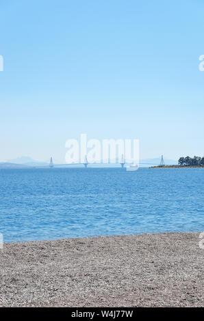 Rio Antirrio bridge silhouette and sailboat .View from Nafpaktos - Stock Photo
