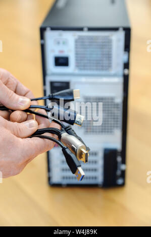 There are various cords and plugs in the hands of a man. - Stock Photo