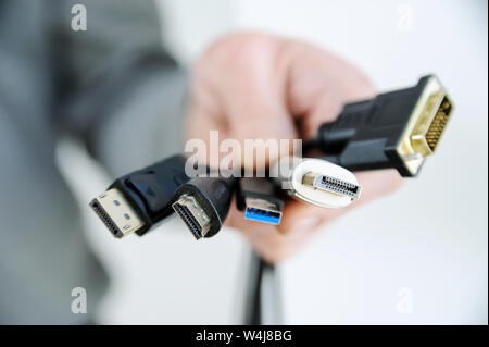 There are various cords and plugs in the hand of a man. - Stock Photo