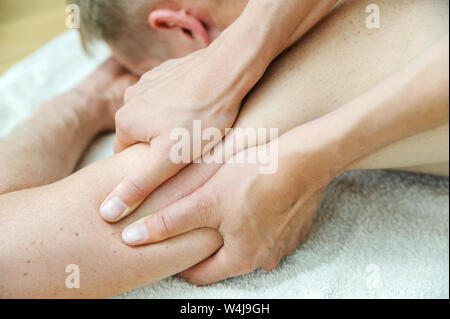 Health massage therapy. Female hands are massaging the man's arm. - Stock Photo