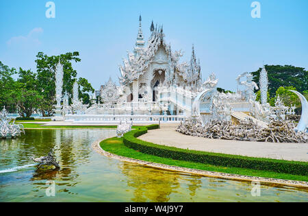 Explore one of the most strange and well known Buddhist temples of Thailand - Wat Rong Khun or White Temple, famous for its unique stucco sculptures, - Stock Photo