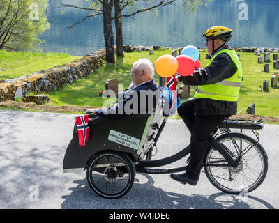 Celebration of the norwegian national day, handicapped elder people join in a special bike, village Hafslo at lake Hafslovatn, located near the Sognef - Stock Photo