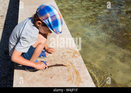 Squatting child drawing with wet twig on marble pool edge - Stock Photo