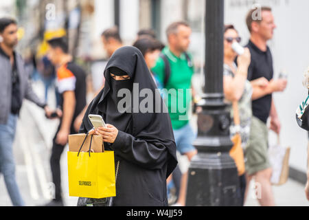 London, UK, July, 2019. A Muslim woman in London wearing a niqab, using mobile phone while shopping. Oxford Street - Stock Photo