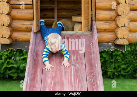Cute adorable caucasian toddler boy having fun sliding down wooden slide at eco-friendly natural playground at backyard in autumn. Playful funny child - Stock Photo