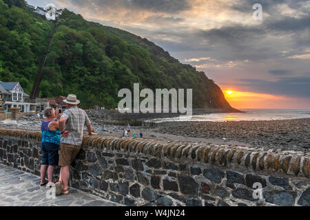 Lynmouth Harbour, North Devon, England. Tuesday 23rd July 2019. UK Weather. The calm before the storm. After a hot summers day in North Devon, at sunset people still play on the beach as a couple record the colourful sunset  over the picturesque little harbour in Lynmouth. Credit: Terry Mathews/Alamy Live News - Stock Photo