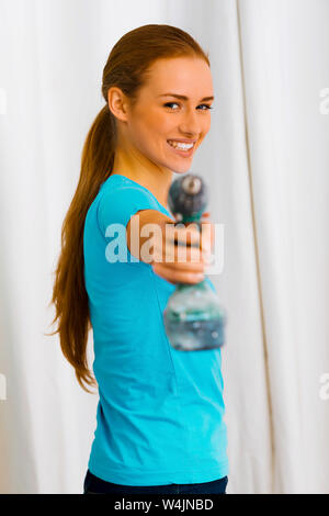 Young smiling woman standing with an electric screwdriver in home interior. - Stock Photo