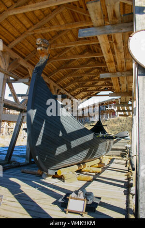 Ancient Scandinavian wooden ship of the Vikings Drakkar under a canopy in the open-air museum. Drakkar with hand-carved dragon's head on the nose, oar - Stock Photo
