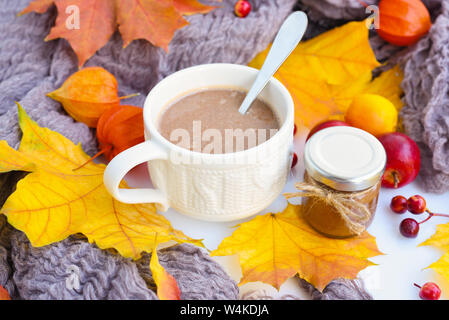 Autumn composition. Fall leaves, cup of coffee, chocolate paste jar and scarf on white background. - Stock Photo