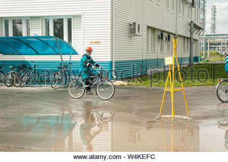 Tobolsk, Russia - July 15. 2016: Sibur company. Man in working uniform goes by bicycle - Stock Photo
