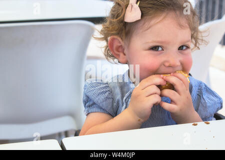 Cheeky little girl eating food looking at the camera smiling - Stock Photo