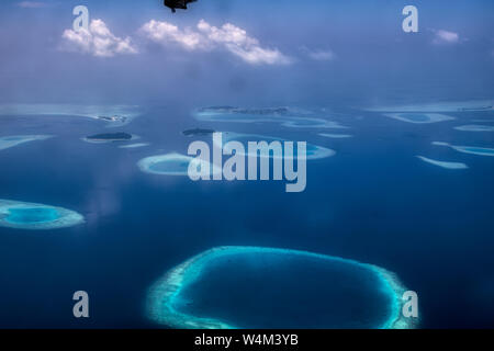 This unique image shows the Maldives photographed from a plane from above. You can see the atolls in the sea well.