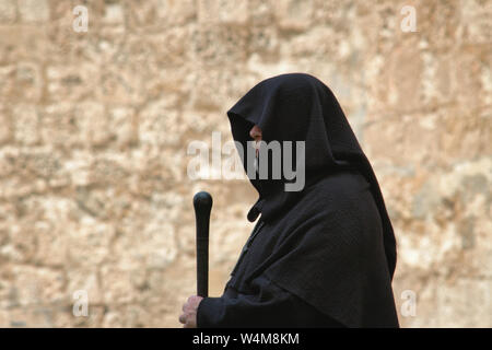 Hooded spooky looking medieval monk in a traditional black robe with staff - Stock Photo