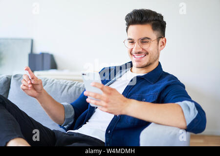 Picture of young man sitting on sofa at home and paying for shopping online with smartphone and credit card - Stock Photo
