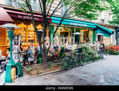 Paris, France - May 8, 2016: People enjoy a cafe and conversation at a quiet and charming tree-lined street in the bohemian Marais district of Paris, - Stock Photo