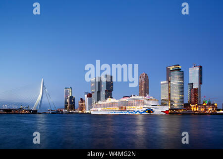 Rotterdam, Netherlands – June 27, 2019: Cruise ship Aida Perla moored at the Wilhelminapier on the Kop van Zuid in Rotterdam at dusk with the Erasmus - Stock Photo