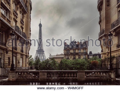View of the Eiffel Tower from a small cobbled dead-end street of the Chaillot hill on a rainy day with Haussmann style architecture on the foreground. - Stock Photo