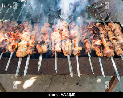 cooking many shish kebabs (shashlyk) from pork meat on brazier outdoors - Stock Photo