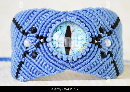 blue bracelete with white beads and the dragon's eye on the hand from waxed thread in the technique of macrame. Handmade - Stock Photo