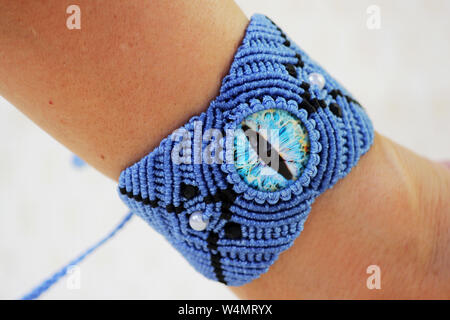 blue bracelete with white beads and the dragon's eye on the hand from waxed thread in the technique of macrame. Handmade. put on hand. - Stock Photo