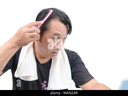 Middle-aged asian man worry about his  hair loss or alopecia isolated on white background, Health care concept - Stock Photo