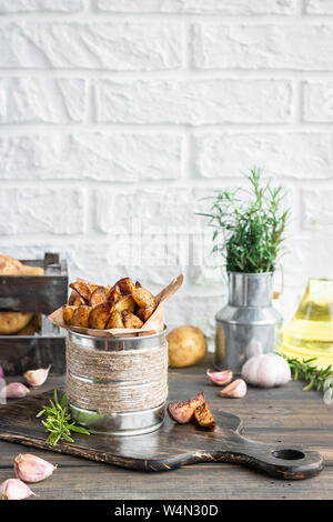 Baked young potatoes in a rustic style with rosemary, garlic and sumac as a concept of simple and delicious food and an alternative to french fries. - Stock Photo