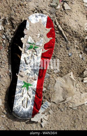 The flag of Syria is depicted on the sole of an old boot. Ecology concept with environmental pollution from household and industrial waste. - Stock Photo