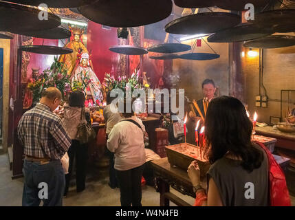 Worshippers in Man Mo Temple, a Taoist temple on Hollywood Road, Sheung Wan, Central district, Hong Kong Island, Hong Kong, China - Stock Photo