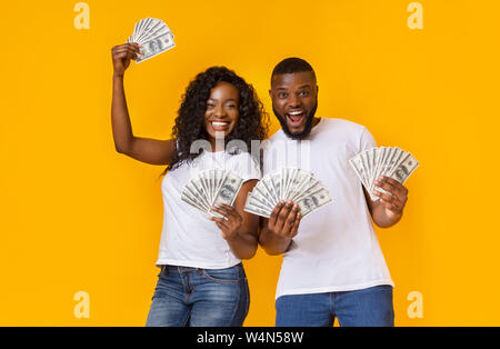 Lucky afro man and woman holding winning money - Stock Photo