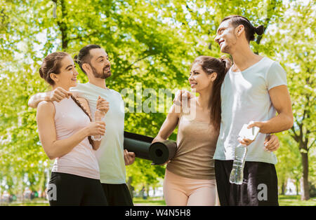 Happy friends resting and chatting after yoga class in park. - Stock Photo