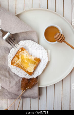 Flat lay view of kitchen decor details and delicious toast with fresh butter and honey alongside a little bowl of honey on white background. - Stock Photo