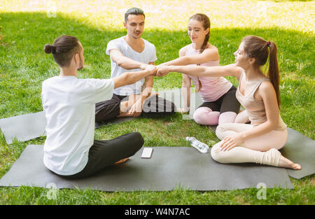 Group of fit happy people fist bumping, celebrating success. - Stock Photo