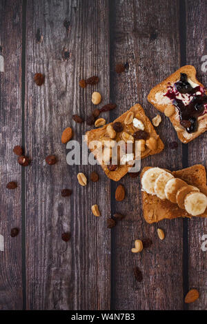 Close-up of morning toasts with different types of toppings on wooden background. - Stock Photo