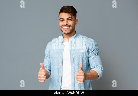 Smiling Guy Showing Thumbs Up With Both Hands - Stock Photo