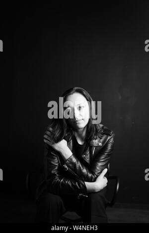 Studio portrait of an attractive young woman in a black leather jacket against a plain background - Stock Photo