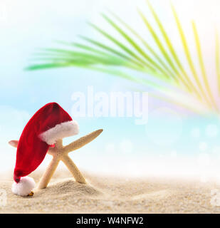 Starfish in Santa hat on the summer beach. Christmas concept. - Stock Photo
