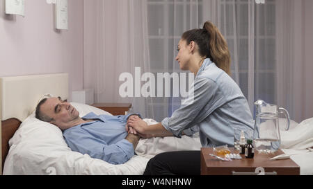 Daughter visiting elderly father in hospital and medical worker talking to them - Stock Photo