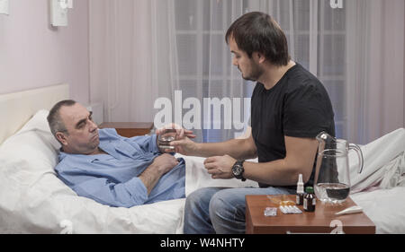 Son visiting elderly father in hospital and medical worker talking to them - Stock Photo