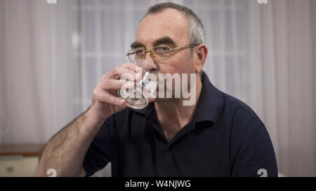 elderly man drinks water, emotions of joy and happiness - Stock Photo