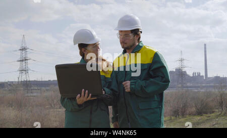 Workers in production plant as team discussing, industrial scene in background - Stock Photo