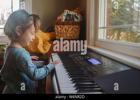 portrait of a cute little child playing piano in front of a window