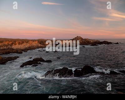 Ocean waves crashing on rocks at sunset - Stock Photo