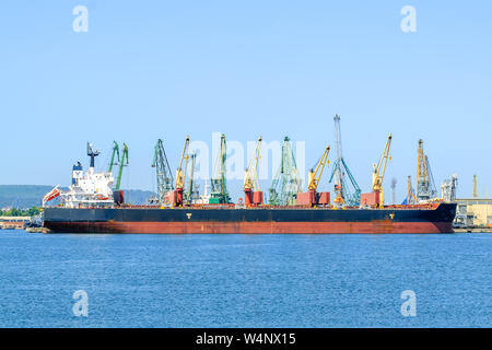 Varna, Bulgaria, July 22, 2019. Large red black sea cargo ship while parking in the port. Port cranes download the cargo into the ship. - Stock Photo