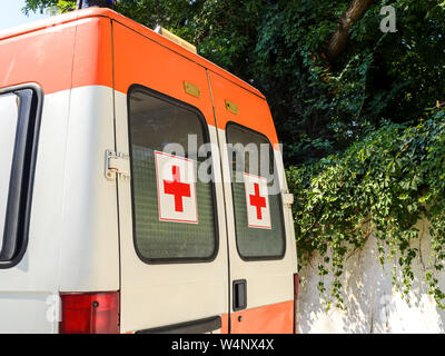 Varna, Bulgaria, July 22, 2019. Stationary white ambulance car with red crosses on the windows on a sunny summer day. Emergency medical service van. - Stock Photo