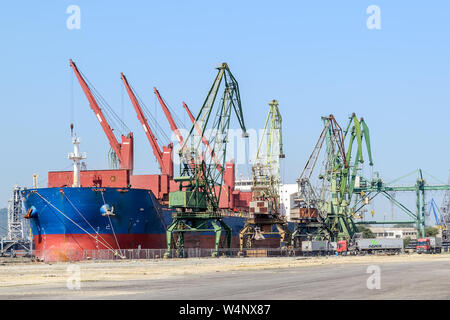 Varna, Bulgaria, July 22, 2019. Large blue red sea cargo ship while parking in the port. Port cranes download the cargo into the ship. - Stock Photo