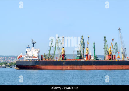 Varna, Bulgaria, July 22, 2019. Large black red sea cargo ship while parking in the port. Port cranes download the cargo into the ship. - Stock Photo