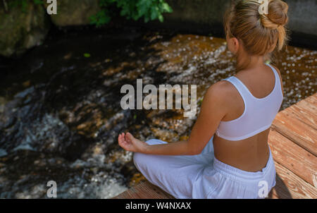 Attractive woman is practicing yoga and meditation sitting in lotus pose near waterfall. Young woman is meditating outdoors in morning. - Stock Photo