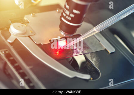 Microscope in medical laboratory analyzing a test sample - Stock Photo