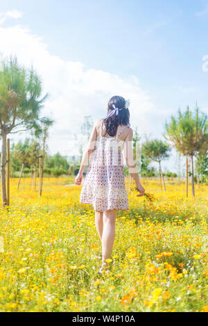 Rear view of a beautiful woman in dress walking through a field of flowers carrying her shoes - Stock Photo