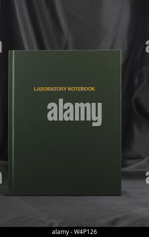 Conceptual image of importance of data and research in Laboratory Notebook placed against black background in vertical photo with copy space. - Stock Photo